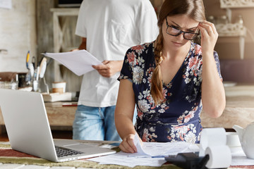 Concerned young female in eyewear, can`t understand how make financial report, sits at kitchen table with documents and laptop computer, realizes that they are short of money, calculate figures
