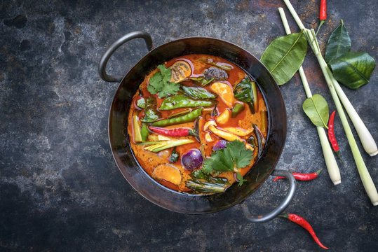 Traditional Thai kaeng phet red curry with vegetables as top view in a wok with copy space left
