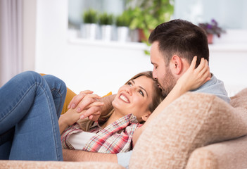 Young couple in hug on sofa