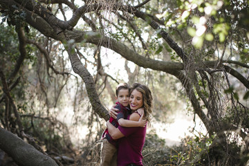 Portrait of son embracing smiling mother against branches at forest