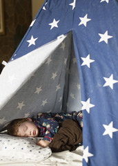 Boy sleeping on bed in tent at home