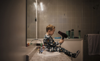 Side view of boy holding hair dryer while sitting by bathroom sink at home