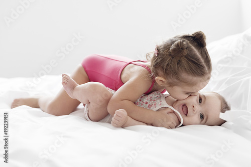 Girl Kissing Sister Lying On Bed At Home