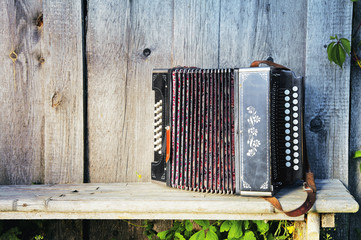 Old lonely accordion on the bench