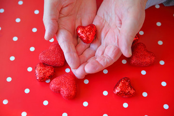 Man with shiny heart in hands over more hearts on polka dot background