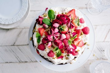 Cake topped with strawberries, raspberries and pink rose petals
