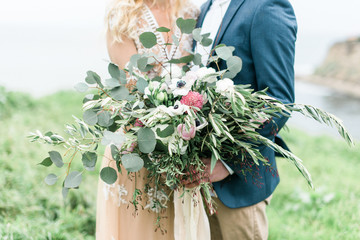 Couple holding bouquet of flowers in field