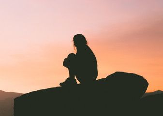 Silhouette of woman sitting on rocks at sunset