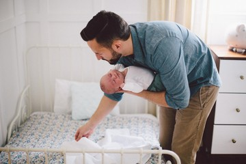 Father holding sleeping infant child over bed in nursery