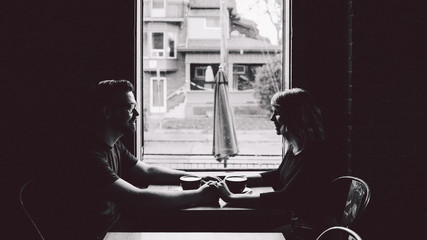 Couple holding hands in dark cafe