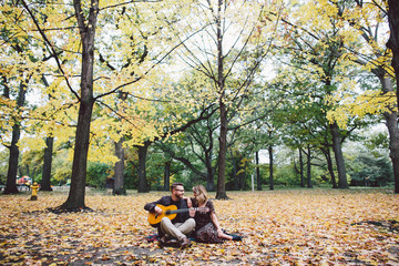 Couple sitting in park and playing guitar