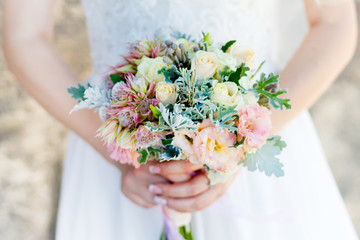 A wedding bouquet in the hand. A bouquet of flowers as a symbol of love is held by a couple in love during the wedding