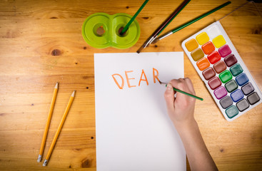 kids hand drawing a greeting on blank page, top view