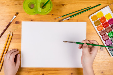 kids hand holding a paintbrush on blank page, top view