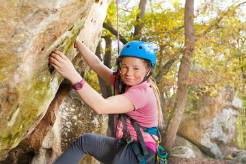 Young rock climber exercising outdoors in forest