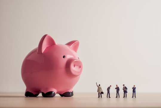 Conceptual image of business people looking at giant Piggy Bank