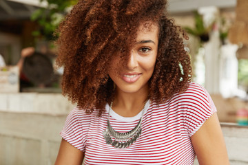 Headshot of adorable dark skinned female has luxurious curly hair, charming smile, demonstrates perfect teeth, being satisfied with service in restaurant, enjoys spare time together with boyfriend