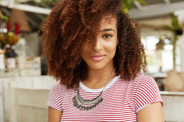 Fashionable dark skinned female model with stylish Afro hairdo, poses at camera against cafe interior, spends dinner break alone, likes to be photographed. People, ethnicity and beauty concept