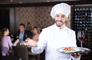 chef with dishes on serving tray welcoming