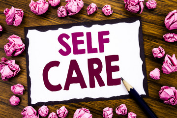 Hand writing text caption inspiration showing Self Care. Business concept for Taking caring for own Health Written on sticky note paper, wooden background folded pink paper meaning thinking