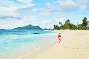 Woman with sarong walking on beach Anse Nord Est at Seychelles, Mahe
