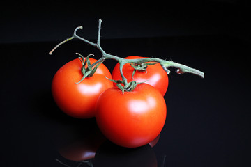 Tomato on black reflective studio background. Isolated black shiny mirror mirrored background for every concept.