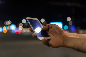 male hand holding touch screen mobile phone on blurred night-lights