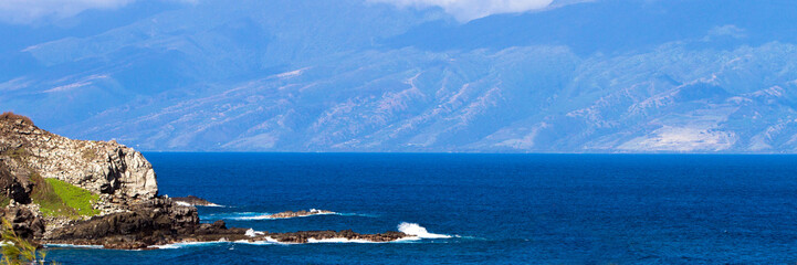Panorama of volcanic rock and Pacific surf on the coast of Maui, Hawaii, with Molokai in the distance