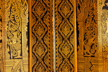 Traditional Thai art of golden painting on the door in Thailand temple