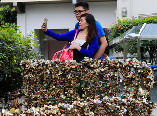 "A couple takes a selfie in front of ""Love Lock"" fence, the symbol of undying love with God, near the National Shrine of Our Mother of Perpetual Help in Paranaque city, as part of Valentine's Day celebrations, Metro Manila"