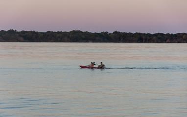 Personas remando en un kayak por la tarde en un rio