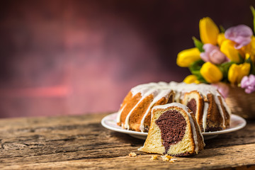 Easter Cake. Traditional ring marble cake withe easter decotation. Easter eggs and spring tulips.
