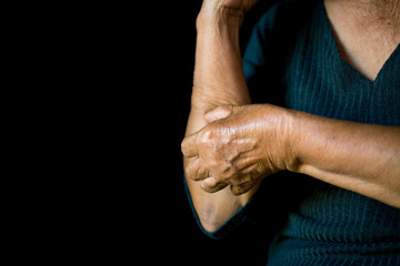 Old hands itching on arm in black background, dermatitis concept