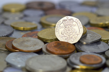 British twenty pence coin on top of a large pile of coins