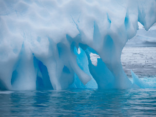 Close Up of a light and medium blue iceberg with divots, holes and spikes. It is in the Southern Ocean in Antarctica.
