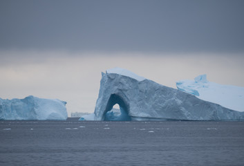A wedge shaped iceberg with a arched opening floating in the gray water of the Southern Ocean with a bank of dark gray clouds above,