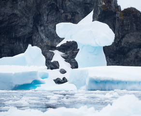 A light blue ice formation on a pedestal. A rocky cliff is in the background.