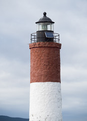Lighthouse in Beagle Channel painted rust and white. A solar panel is near the top of the structure.