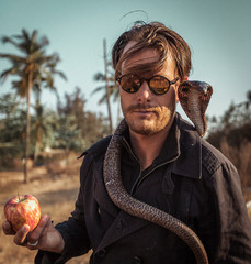 Portrait of hipster poet in trench coat with apple in the hand and cobra around his neck