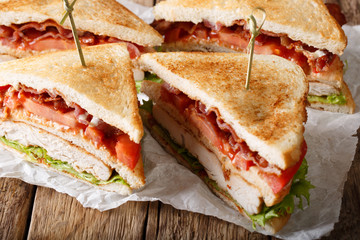 layer club sandwich with turkey meat, bacon, tomatoes and lettuce macro. horizontal