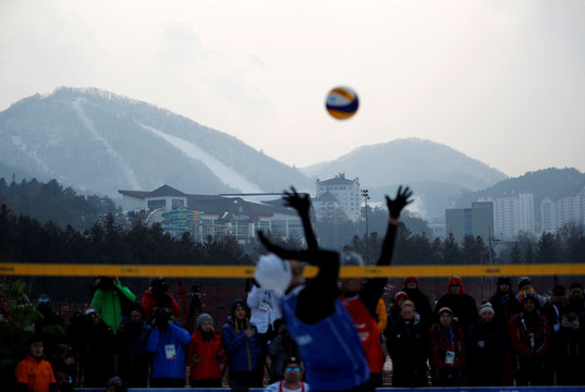 Snow-covered slopes are seen in the background as players play during an event promoting the Snow Volleyball hosted by FIVB and CEV in Pyeongchang