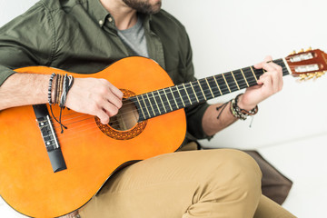 cropped image of man sitting and playing acoustic guitar
