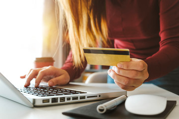 Business woman hands using laptop and holding credit card with digital layer effect diagram as Online shopping concept