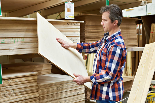 Man chooses plywood boards in store