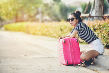 The girl is sitting on the street with her pink suitcase ready to travel.