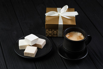marshmallow on a black table with golden gift box and coffe cup