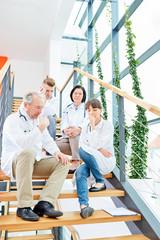 Ärzteteam sitzt auf einer Treppe im Krankenhaus