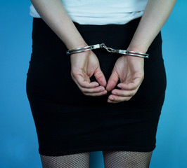 A prostitute with cuffs in front of her. She was arrested while serving clients