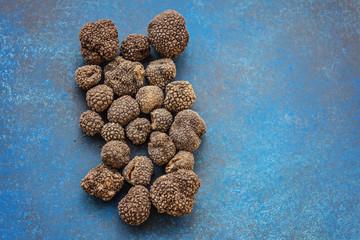 Black truffles on a modern blue surface