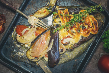 Close-up of stuffed aubergines, tomatoes, meat and onion with sauce on the dish. Art.